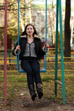 Woman wearing sitting on a swing in a park. Young woman wearing sitting on a swing in a park Royalty Free Stock Photo