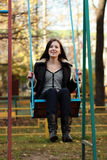Woman wearing sitting on a swing in a park. Young woman wearing sitting on a swing in a park Royalty Free Stock Photos