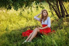 Woman wearing skirt sitting under the tree Royalty Free Stock Photo
