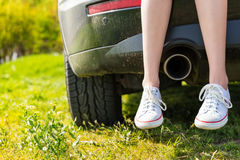 Woman Wearing Sneakers Sitting on Tailgate of Car. Close Up of Woman Wearing Sneakers Sitting with Crossed Ankles on Rear Tailgate of Vehicle with View of stock photos