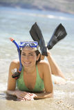 A woman wearing snorkeling equipment lying on a beach Royalty Free Stock Image