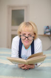 The woman wearing spectacles reads the book Stock Photo