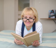 The woman wearing spectacles reads the book Royalty Free Stock Photo
