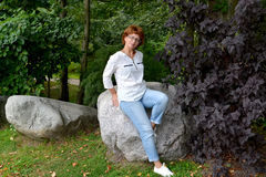 The woman wearing spectacles sits on a boulder in the park Royalty Free Stock Photos