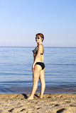 Woman wearing spectacles sunbathes about the sea. The harmonous woman wearing spectacles and in a bathing suit sunbathes about the sea, standing on sand and Royalty Free Stock Images