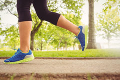 Woman wearing sport shoes jogging in park Stock Photo