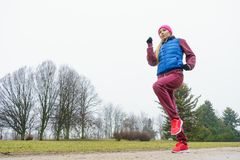 Woman wearing sportswear exercising outside during autumn Stock Images