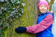 Woman wearing sportswear hugging tree royalty free stock photography