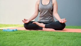 Woman wearing sportswear practicing yoga on orange mat on green grass. wellness concept.