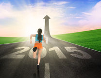 Woman wearing sportswear run on the road. Rear view of young woman running on the road with number 2015 Stock Photos