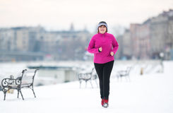 Woman wearing sportswear and running on snow during winter Royalty Free Stock Images