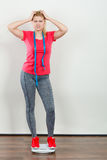 Woman wearing sportswear standing on weight machine Stock Images