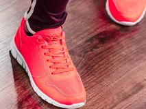 Woman wearing sportswear trainers shoes. Woman wearing sportswear trainers red shoes, comfortable footwear perfect for workout and training Royalty Free Stock Images
