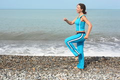 Woman wearing sporty clothers is making exercise Royalty Free Stock Image