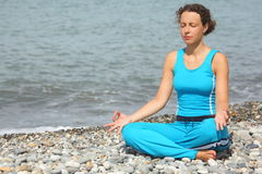 Woman wearing sporty clothers is meditate on sea Stock Image
