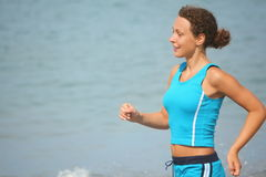 Woman wearing sporty clothers is running near sea Stock Images