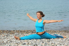 Woman wearing sporty clothers stretching on sea Stock Photos
