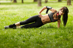 Woman wearing sporty clothes doing fitness exercise on green grass. Young beautiful brunette woman wearing sporty clothes doing fitness exercise on green grass Stock Photo