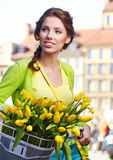 Woman wearing a spring skirt like vintage. Pin-up holding bicycle with some yellow  flowers in the basket in old town Royalty Free Stock Photos