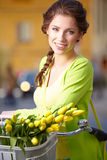 Woman wearing a spring skirt like vintage pin-up holding bicycle. With some yellow  flowers in the basket in old town Royalty Free Stock Photos