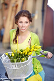 Woman wearing a spring skirt like vintage pin-up holding bicycle. With some yellow  flowers in the basket in old town Royalty Free Stock Photo