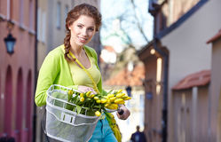Woman wearing a spring skirt like vintage pin-up holding bicycle. With some yellow  flowers in the basket in old town Royalty Free Stock Photography