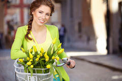 Woman wearing a spring skirt like vintage pin-up holding bicycle. With some yellow  flowers in the basket in old town Stock Images