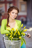 Woman wearing a spring skirt like vintage pin-up holding bicycle. With some yellow  flowers in the basket in old town Stock Photography