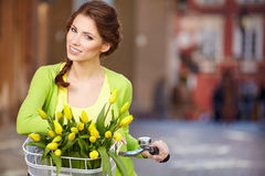 Woman wearing a spring skirt like vintage pin-up holding bicycle. With some yellow  flowers in the basket in old town Stock Photo