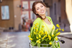 Woman wearing a spring skirt like vintage pin-up holding bicycle. With some yellow  flowers in the basket in old town Stock Photos