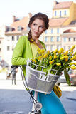Woman wearing a spring skirt like vintage pin-up holding bicycle. With some yellow  flowers in the basket in old town Stock Image