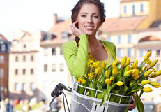 Woman wearing a spring skirt like vintage pin-up holding bicycle. With some yellow  flowers in the basket in old town Royalty Free Stock Image