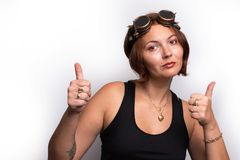 Woman wearing steampunk glasses displaying thumbs up. Positive mood on royalty free stock photography