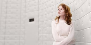 Woman wearing straight-jacket. Half body portrait of attractive young woman restrained in straight-jacket with padded white cell wall background royalty free stock image