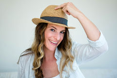 Woman wearing a straw fedora smiling into the camera Royalty Free Stock Photography