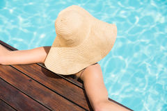 Woman wearing straw hat leaning on wooden deck by poolside Royalty Free Stock Images