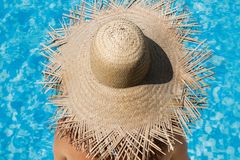 Woman wearing a straw hat by the pool stock photos
