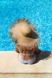 Woman wearing a straw hat by the pool royalty free stock photos