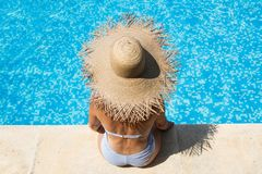 Woman wearing a straw hat by the pool stock photography