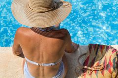 Woman wearing a straw hat by the pool royalty free stock photo