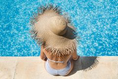 Woman wearing a straw hat by the pool stock photo
