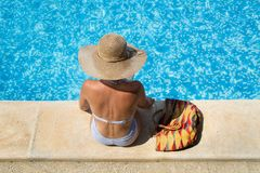 Woman wearing a straw hat by the pool royalty free stock images