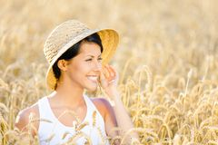 Woman wearing straw hat is in rye field Royalty Free Stock Image