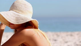 Woman wearing a straw hat and sitting on the beach Royalty Free Stock Image