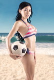 Woman wearing striped bikini holds soccer ball Stock Photos