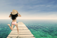 Woman wearing striped bikini running at pier Stock Photography