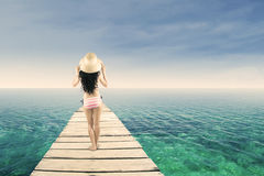 Woman wearing striped bikini standing at pier Royalty Free Stock Photos