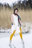 Woman wearing a stylish dress, scarf and ice skate Stock Photo