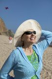 Woman wearing summer hat on beach Stock Images