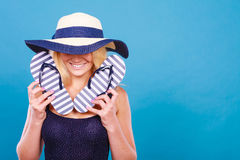 Woman wearing sun hat, holding flip flops Royalty Free Stock Photography